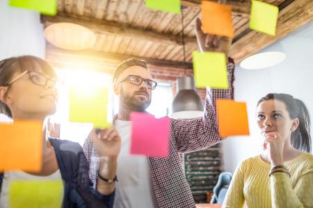 Los empresarios se reúnen en la oficina y usan notas adhesivas para compartir ideas. Concepto de lluvia de ideas. Nota adhesiva en la pared de cristal.