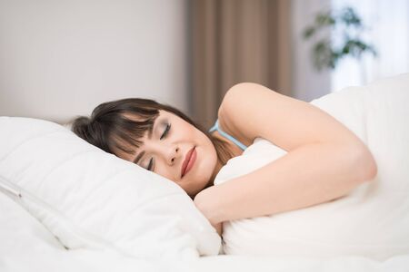Beautiful young woman sleeping on a bed in the bedroom. A peaceful sleep makes you happy.