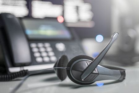 Communication support, call center and customer service help desk. VOIP headset on laptop computer keyboard. Stock Photo