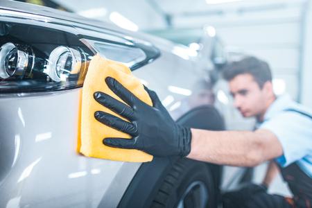 Auto-Detaillierung - der Mann hält die Mikrofaser in der Hand und poliert das Auto. Selektiver Fokus Standard-Bild - 89441369