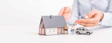 Verzekering huis, auto en familie gezondheid leven concept. De verzekeringsagent presenteert het speelgoed dat de dekking symboliseert. Stockfoto