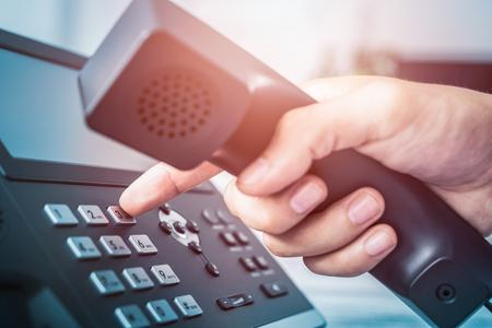 コミュニケーションサポート、コールセンター、カスタマーサービスヘルプデスク電話のキーパッドを使用する。 写真素材