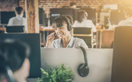 Call Center Worker begleitet von ihrem Team. Lächelnder Kundensupport bei der Arbeit. Junge Angestellte arbeiten mit einem Headset.