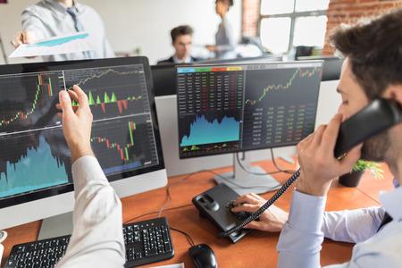 Inwestowanie w zespołowe transakcje inwestycyjne odbywa się na giełdzie. Osoby pracujące w biurze. Zdjęcie Seryjne