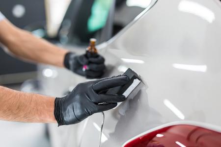 Auto detailing - Man past nano beschermende coating toe op de auto. Selectieve focus.