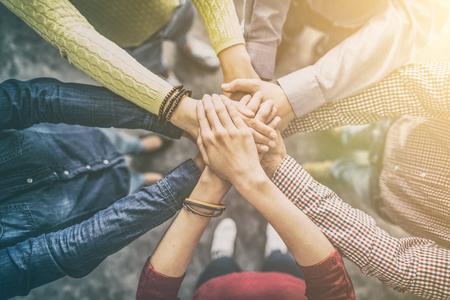 Zamyka w górę odgórnego widoku młodzi ludzie biznesu stawia ich ręki wpólnie. Stos rąk. Koncepcja jedności i pracy zespołowej.
