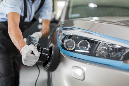 Car detailing - Man holds a polisher in the hand and polishes the car. Selective focus. Stock Photo