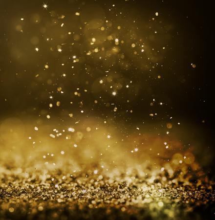 glitter glittering background light shimmering gold golden shine spark shimmer yellow pattern dust bright glitz concept - stock image