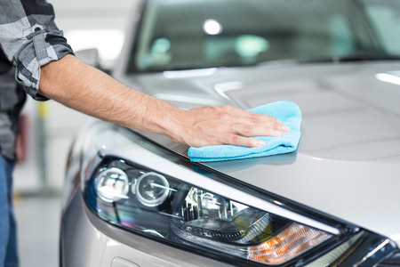 valeting: Car detailing - the man holds the microfiber in hand and polishes the car. Selective focus.