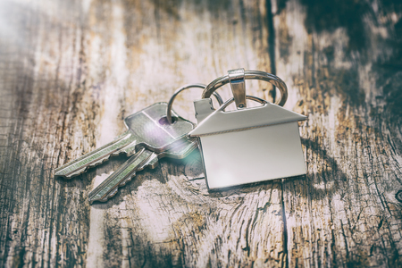 House key on a house shaped keychain on wooden table. Concept for real estate or renting home. Stock Photo - 89618894