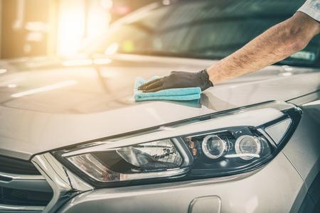 Detalhamento do carro - o homem segura a microfibra na mão e polida o carro. Foco seletivo. Foto de archivo - 89618922