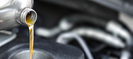Giet olie naar de auto-motor. Verse olie wordt gegoten tijdens een olieverversing naar een auto.