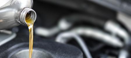 Wylewanie oleju do silnika samochodowego. Świeży olej wylany podczas zmiany oleju w samochodzie. Zdjęcie Seryjne