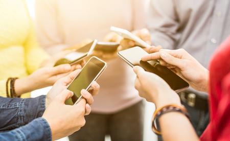 Groep jonge hipsters die telefoon in handen houden. Vrienden hebben plezier samen met smartphones.
