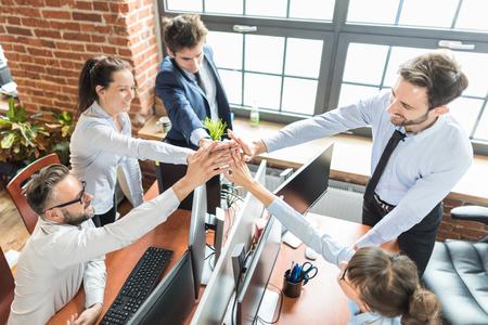 Persone d'affari felice mostrando il lavoro di squadra e dare cinque in ufficio. Concetti di lavoro di squadra.