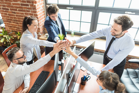 Business people happy showing team work and giving five in office. Teamwork concepts. Archivio Fotografico