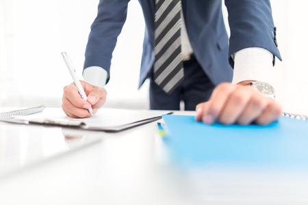 Business man signing contract document on office desk, making a deal.
