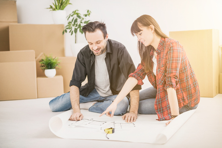 A young couple plan analyzes the new apartment. They look at a blueprint of the house and talk about the future. Moving is the main theme. Stock Photo