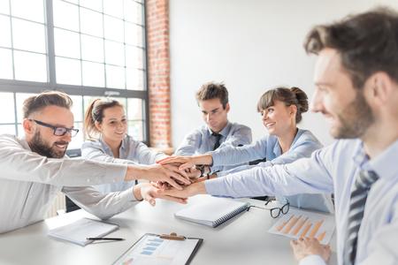 Feche a vista superior dos jovens empresários juntando as mãos. Pilha de mãos. Unidade e conceito de trabalho em equipe.