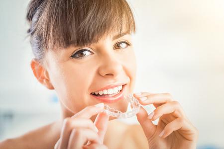 Vrouw die orthodontische siliconetrainer draagt. Onzichtbare beugels aligner. Mobiel orthodontisch apparaat voor tandcorrectie. Stockfoto