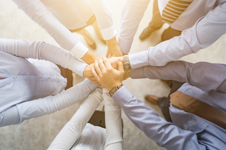 Close up top view of young business people putting their hands together. Stack of hands. Unity and teamwork concept.