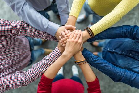 Close up vista superiore di giovani imprenditori mettendo le mani insieme. Pila di mani. Unità e concetto di lavoro di squadra.