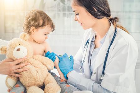 Mujer joven pediatra realiza una vacunación de una pequeña chica . la chica está sosteniendo una nuez Foto de archivo - 93002396