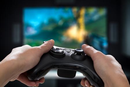 Spielspielspielfernsehspaßgamer gamepad Kerlprüfervideokonsole, die den Spieler hält spielerisches Genuss-Ansichtkonzept des Hobbys - Archivbild spielt