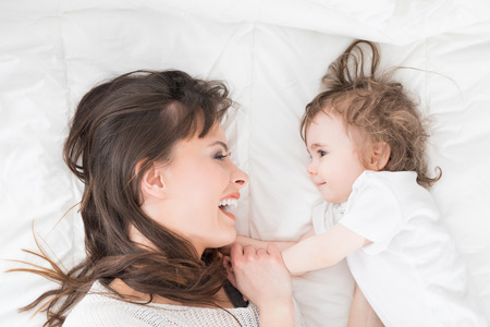 Young, beautiful and smiling mother with baby girl. Daughter close to loving mom.