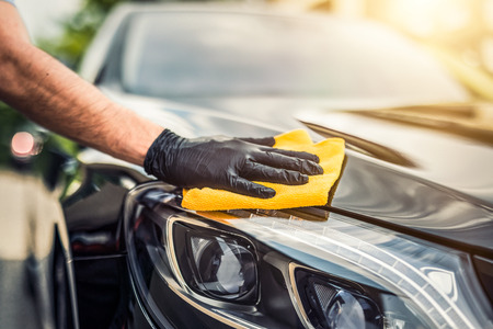 Car detailing - mężczyzna trzyma w ręku mikrofibrę i poleruje auto. Selektywna ostrość.