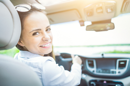Beautiful young woman sitting in the interior of a new car with a smile. He is glad he is a driver. Stock Photo