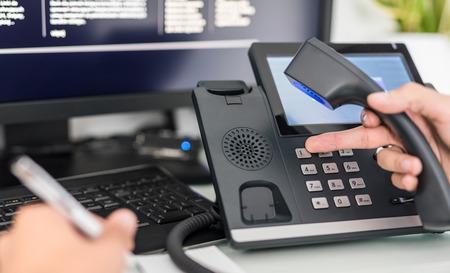 Wsparcie komunikacyjne, call center i help desk. Zestaw słuchawkowy VOIP na klawiaturze laptopa. Zdjęcie Seryjne