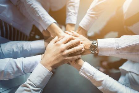 若いビジネスマンが手をつないでトップビューをクローズアップ。手の積み重ね統一とチームワークのコンセプト。