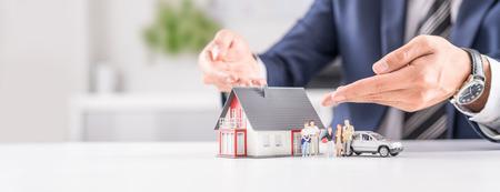 Versicherungshaus-, Auto- und Familiengesundheit leben Konzept. Der Versicherungsagent präsentiert die Spielzeuge, die die Deckung symbolisieren.