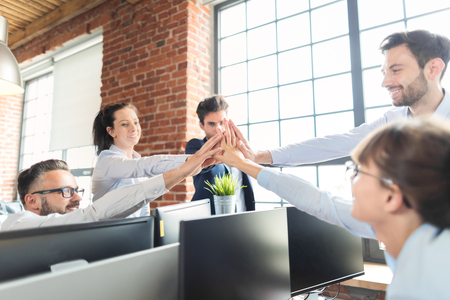 Business people happy showing team work and giving five in office. Teamwork concepts. Stock Photo