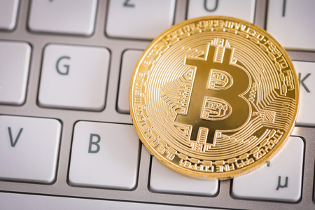 Bitcoin gold coin on computer keyboard. Virtual cryptocurrency concept. Stock Photo
