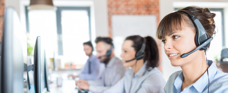 Call center worker accompanied by her team. Smiling customer support operator at work. Young employee working with a headset.