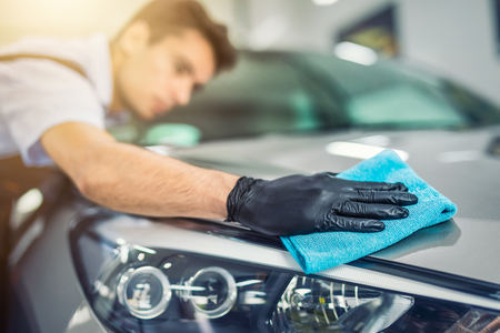 the man holds the microfiber in hand and polishes the car. Selective focus.