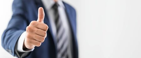 Business man shows thumb up sign gesture. Isolated on grey background. Stock Photo