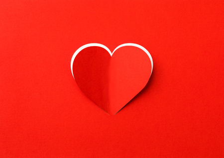 Valentines Day background. A red sheet of paper with a cut out heart. White background.