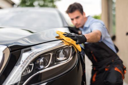 Detalles del auto: el hombre sostiene la microfibra en la mano y pule el auto. Enfoque selectivo Foto de archivo