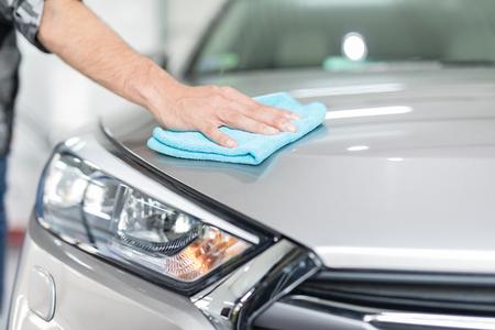 車のディテール - 男は手にマイクロファイバーを保持し、車を磨きます。選択的な焦点。