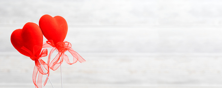 Valentines Day background. Two red hearts with a bow on a wooden background.