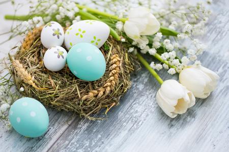 Ostereier im Nest eines Vogels auf einem Holztisch. Blumensymbol des Frühlinges. Standard-Bild - 96035208