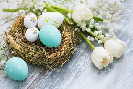 Easter eggs in a bird's nest on a wooden table. Flowers symbol of spring.