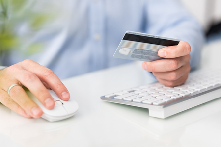 Hands holding credit card and using computer. Online payment and shopping concepts.
