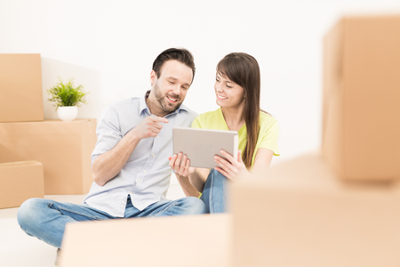 A young couple sitting in a new apartment and uses a digital tablet. Discuss home repair projects while moving. Stock Photo