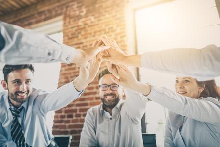 Ludzie biznesu szczęśliwy pokazując pracę zespołową i dając pięć w biurze. Koncepcje pracy zespołowej.