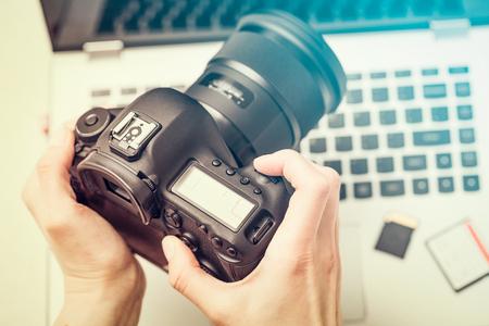 Moderna fotocamera digitale DSLR e workstation computer. Fotografia e concetto di videografia.