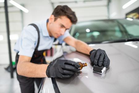 Dettagli dell'auto: l'uomo applica un rivestimento protettivo nano all'auto. Messa a fuoco selettiva. Archivio Fotografico